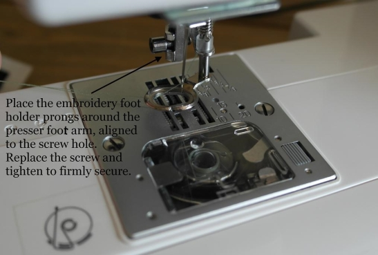 The embroidery foot attached at presser arm screw.