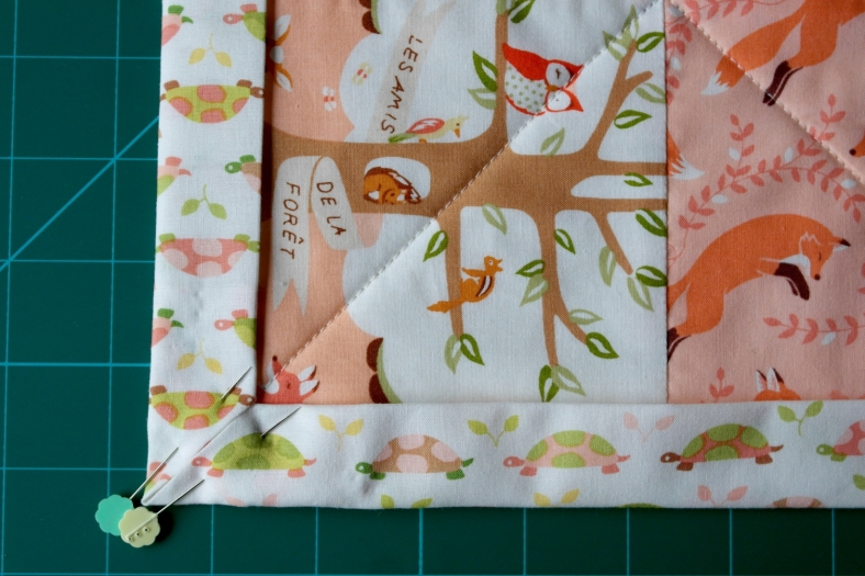 Backing fabric folded over again to overlap quilt top