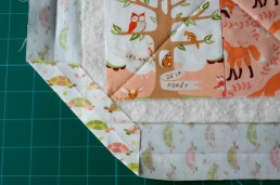 Fold corner to meet quilt top corner